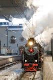 Vecchia locomotiva a vapore nera in Russia nell'inverno sui precedenti della stazione ferroviaria di Mosca Immagini Stock