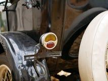 Vecchia luce dei freni dell'automobile riflessione delle foglie cadute sul corpo di vecchia automobile nera fotografie stock
