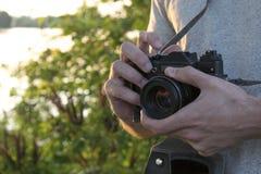 Vecchia macchina da presa in mani maschii Foto al tramonto immagini stock libere da diritti
