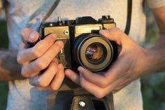 Vecchia macchina da presa in mani maschii Foto al tramonto fotografia stock libera da diritti