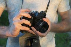 Vecchia macchina da presa in mani maschii Foto al tramonto immagine stock