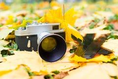 Vecchia macchina fotografica sulle foglie di autunno gialle con le vecchie negazioni vicino Immagini Stock Libere da Diritti