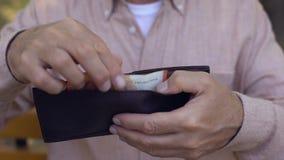 Vecchia mano maschio che mette l'euro portafoglio della fattura, sistema della banca, povertà del pensionato, bilancio stock footage