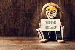 Vecchia marionetta con un'insegna con il depressi di infanzia del testo Fotografie Stock