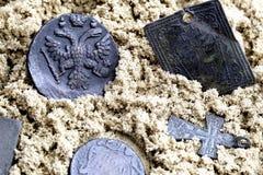 Vecchia moneta con l'aquila a due punte ed i simboli della chiesa ortodossa del XVII secolo sulla sabbia bagnata gialla immagini stock libere da diritti