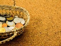 Vecchia moneta internazionale nel canestro sul bordo del sughero immagine stock libera da diritti