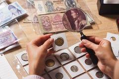 Vecchia moneta nella mano del ` s della donna tramite la lente d'ingrandimento Immagini Stock Libere da Diritti