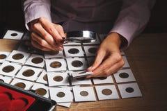 Vecchia moneta nella mano del ` s della donna tramite la lente d'ingrandimento Immagine Stock Libera da Diritti