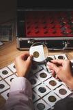 Vecchia moneta nella mano del ` s della donna tramite la lente d'ingrandimento Fotografia Stock