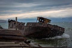 Vecchia, nave arrugginita vicino al pilastro Le grandi onde sommergono la piattaforma Sera nuvolosa di estate immagini stock libere da diritti