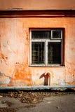 Vecchia parete arancio con una finestra immagini stock libere da diritti