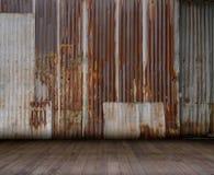 Vecchia parete arrugginita dello zinco con il pavimento di legno, ideale per l'esposizione del prodotto Fotografie Stock Libere da Diritti