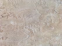 Vecchia parete beige coperta di gesso irregolare Struttura della superficie misera d'annata della pietra della sabbia, primo pian Fotografia Stock