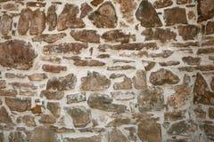 Vecchia parete con molte piccole e grandi pietre Fotografia Stock