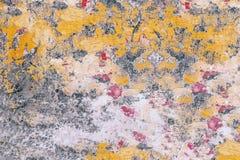 Vecchia parete con pittura sbriciolata: punti rossi, gialli, grigi, bianchi sul primo piano di superficie immagini stock libere da diritti