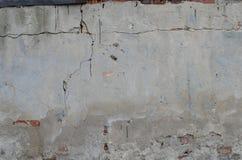 Vecchia parete concreta grigia del garage con i mattoni rossi e le crepe Fotografia Stock
