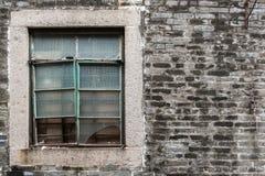 Vecchia parete di mattoni grigia ruvida con la finestra di vetro rotta sporca Facciata della costruzione Fotografie Stock Libere da Diritti