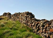 Vecchia parete di pietra con erba verde e cielo blu Fotografia Stock