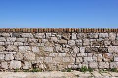 Vecchia parete di pietra con il cielo nei precedenti Immagini Stock
