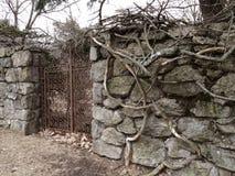Vecchia parete di pietra con il portone del ferro Fotografia Stock