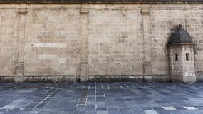 Vecchia parete di pietra del castello da una vecchia via di pietra con una torre immagine stock libera da diritti