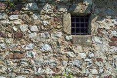 Vecchia parete di pietra di età scura e piccola finestra della cella di prigione con le barre immagini stock
