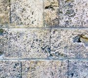 Vecchia parete di pietra invecchiata decomposta della roccia da una costruzione antica fotografie stock libere da diritti