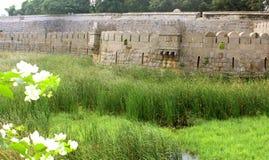 Vecchia parete di pietra ornamentale della fortificazione del vellore con il campo di erba Fotografia Stock