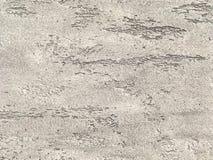 Vecchia parete grigia coperta di gesso irregolare misero Struttura della superficie marrone d'annata della pietra, primo piano Immagine Stock Libera da Diritti