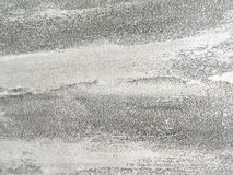 Vecchia parete grigia coperta di gesso irregolare Struttura della superficie d'argento misera d'annata della pietra, primo piano Fotografie Stock