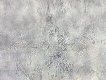 Vecchia parete grigia coperta di gesso irregolare Struttura della superficie d'argento misera d'annata della pietra, primo piano Fotografia Stock