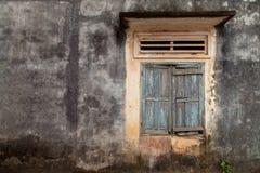 Vecchia parete incrinata con una finestra fotografia stock