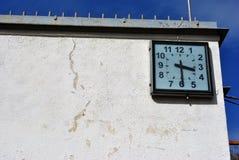 Vecchia parete misera con gli orologi quadrati su cielo blu immagine stock