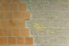 Vecchia parete nociva sporca con le piastrelle di ceramica arancio marroni ed il cemento grigio con le macchie gialle della pittu immagine stock libera da diritti