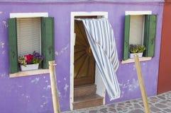 Vecchia parete nociva viola con una porta e le finestre, Burano Fotografia Stock