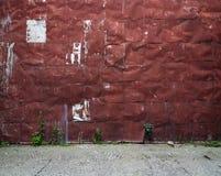 Vecchia parete rivettata del metallo con il pavimento della ghiaia Fotografie Stock Libere da Diritti