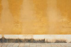 Vecchia parete sbiadita gialla e marciapiede vuoto immagini stock libere da diritti