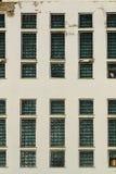 Vecchia parete tagliata misera con le alte finestre del blocco di vetro Fotografia Stock