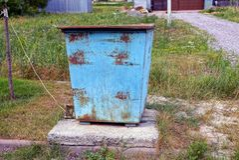 Vecchia pattumiera del ferro all'aperto in erba Fotografia Stock Libera da Diritti