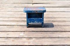 Vecchia piccola sedia blu di legno di pesca sul pilastro di legno di pesca Immagine Stock