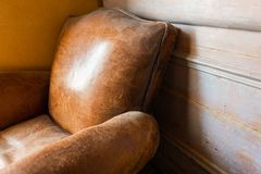 Vecchia poltrona di cuoio d'annata con fondo di legno fotografia stock libera da diritti