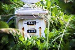 Vecchia, pompa di gas arrugginita e fuori servizio circondata dalle piante Immagine Stock