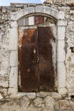 Vecchia porta arrugginita bianca nella parete scalfita Fotografia Stock Libera da Diritti