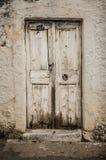 Vecchia porta bianca del legname nella parete scalfita fotografia stock