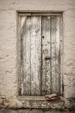 Vecchia porta bianca del legname nella parete scalfita Immagini Stock