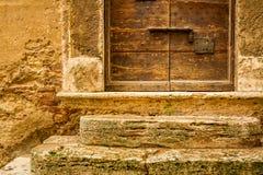 Vecchia porta di legno con il fondo medievale della parete Fotografie Stock Libere da Diritti