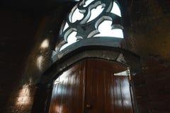 Vecchia porta di legno con una piccola maniglia sul fondo rosso del muro di mattoni, finestra d'annata, raggi di luce Immagini Stock Libere da Diritti