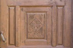 Vecchia porta di legno decorata religiosa in rovina marrone Fotografia Stock