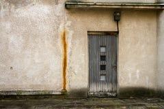 Vecchia porta di legno grigia su una parete fotografia stock