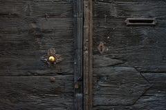 Vecchia porta di legno italiana medievale con la maniglia del metallo e una scanalatura di posta Immagini Stock Libere da Diritti
